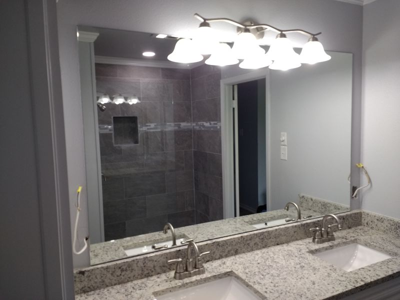 Complete bathroom – vanity mirror with reflection of frameless shower enclosure
