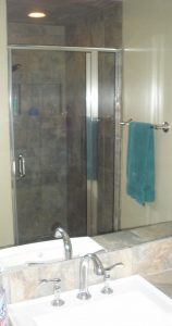 Complete bathroom – vanity mirror with reflection of semi-frameless shower enclosure